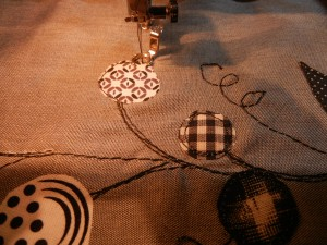 Next, I added circle and leaf shapes: pulling from my black and white fabrics, with Wonder-Under to fuse, a lighter-weight thread to outline and secure.