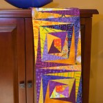 In this piece titled Log Cabin Split Level, purple packs a punch with yellow. This stunner of a runner is by Pamela Dinndorf of Aarvark Quilts; how-to's are in my Quilt Blocks Go Wild!